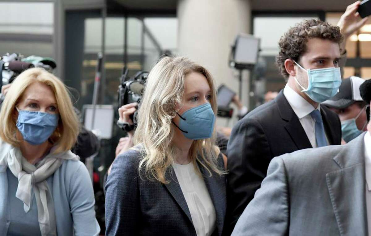 Elizabeth Holmes, center, walks into the federal courthouse for her trial in San Jose. Holmes is accused of duping elite financial backers, customers and patients into believing that her startup was about to revolutionize medicine. If convicted by a jury in San Jose, California, she could be sentenced to 20 years in prison.