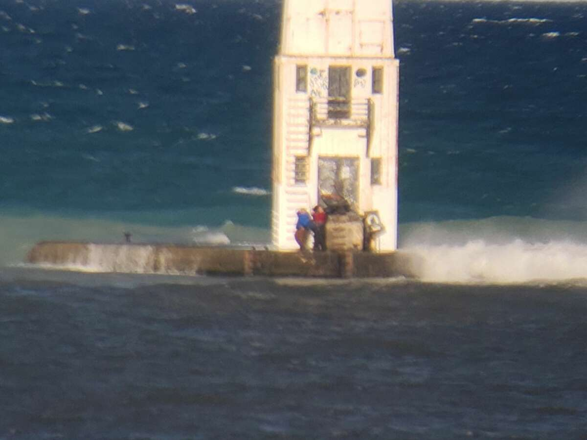 These photos taken by a resident of Frankfort show the Coast Guard rescuing two men trapped at the lighthouse by high waves on Aug. 8.