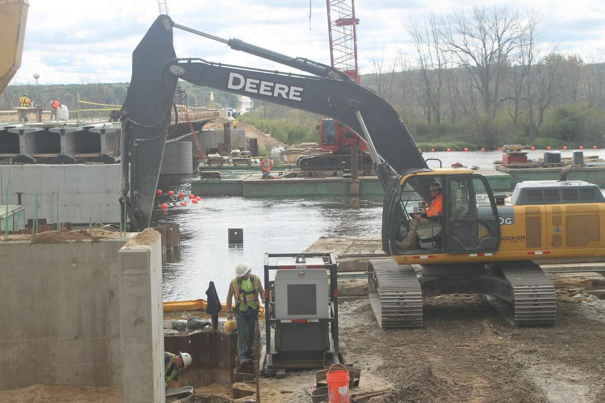 An excavator digs around the bridge abutment at the west end of the M-55 bridge project in Manistee Township on Wednesday.
