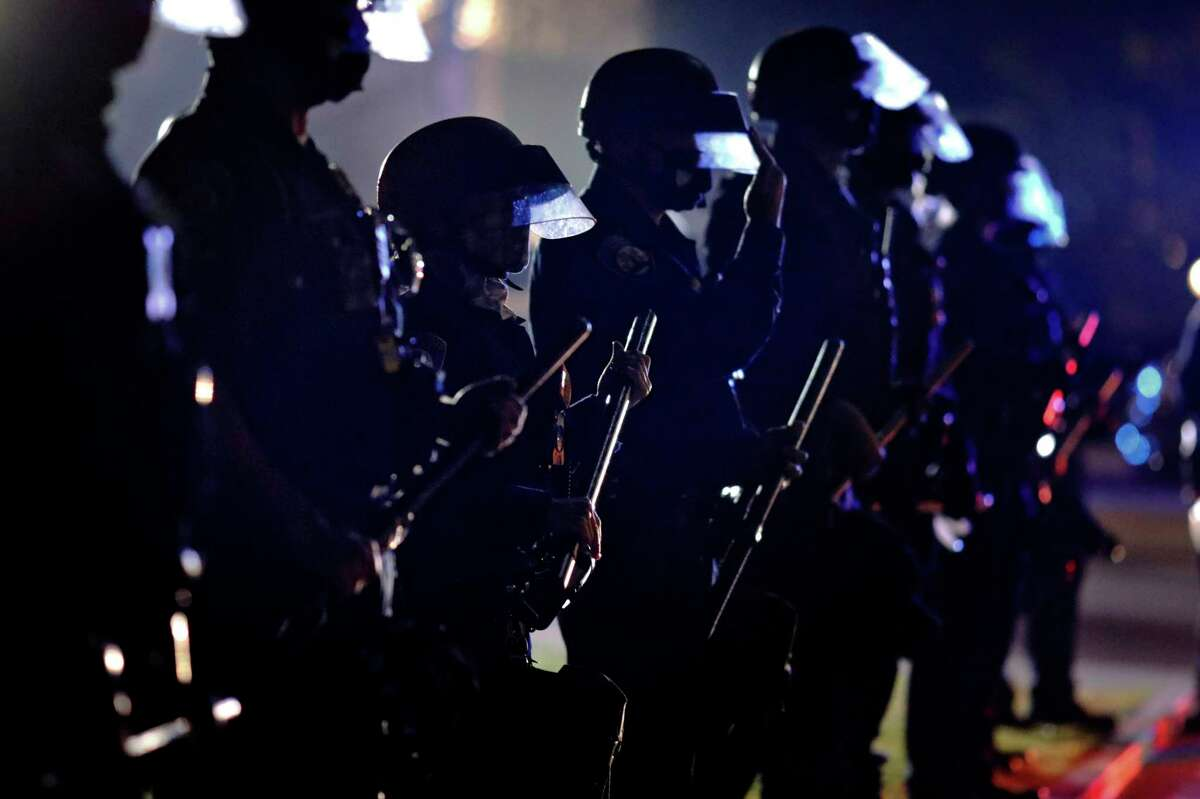 Police hold their clubs as they form a line in front of supporters of President Donald Trump on Nov. 3, 2020, in Beverly Hills. The California Legislatur has given final approval to a bill that would create a process to revoke the licenses of law enforcement officers who commit serious misconduct so they cannot simply move to another department.