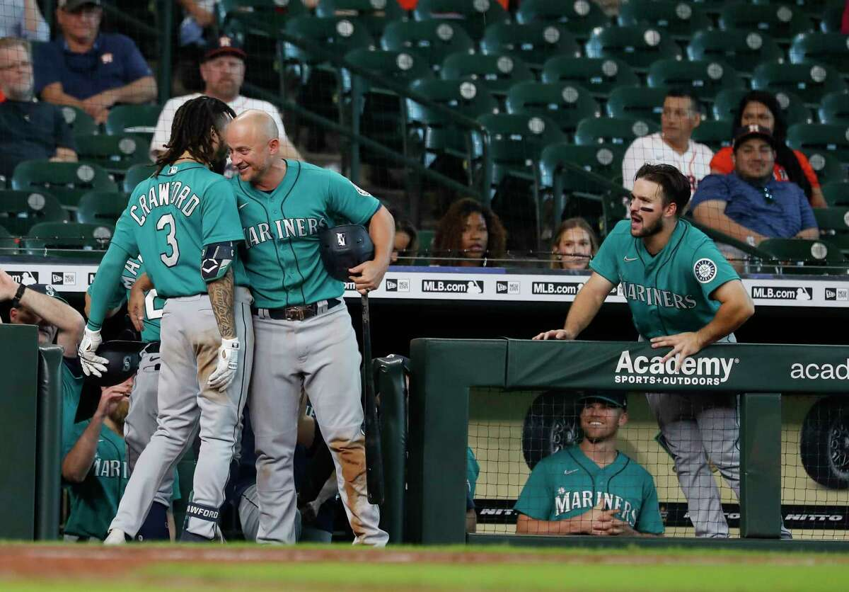 Seattle Mariners J.P. Crawford (3) and Kyle Seager (15) celebrate after Crawford's game winning home run off of Houston Astros relief pitcher Blake Taylor during the ninth inning of an MLB baseball game at Minute Maid Park, Wednesday, September 8, 2021, in Houston. Astros lost the game 8-5.