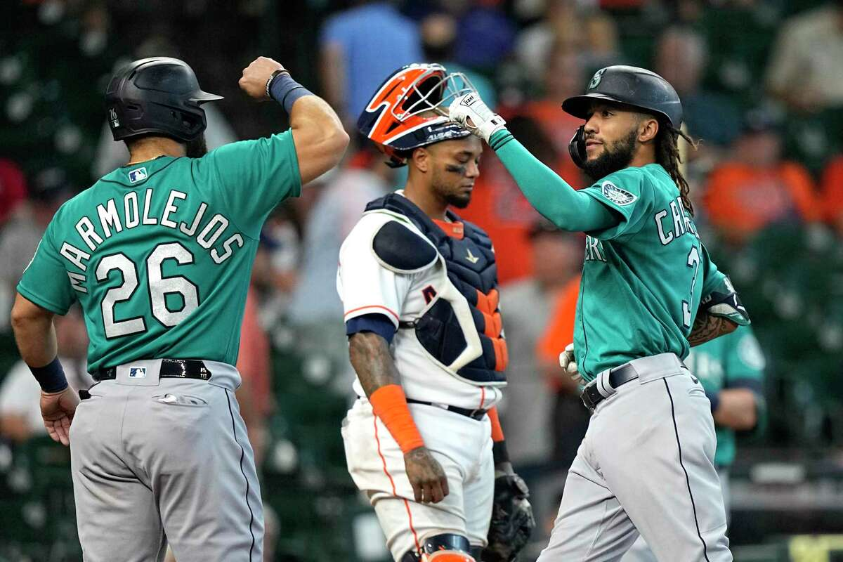 Seattle Mariners' J.P. Crawford (3) celebrates with Jose Marmolejos (26) after both scored on Crawford's two-run home run as Houston Astros catcher Martin Maldonado looks down during the ninth inning of a baseball game Wednesday, Sept. 8, 2021, in Houston. (AP Photo/David J. Phillip)