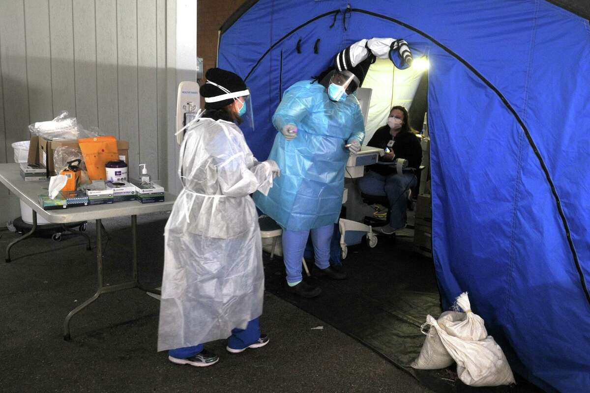 Medical personnel conduct the daily drive-thru COVID-19 testing at Bridgeport Hospital, in Bridgeport, Conn. Dec. 9, 2020.