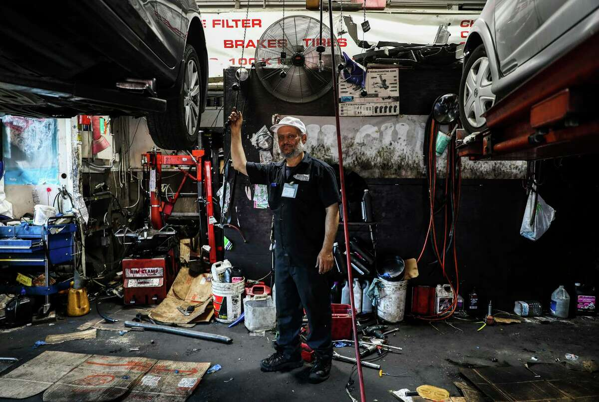 Waheed Alsaidi, owner of Montclair Auto Shop, poses for a portrait inside his garage. He only takes three cars at a time so he can park them inside to deter break-ins.