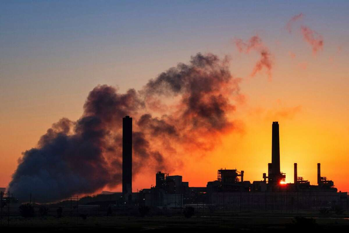 In this July 27, 2018, file photo, the Dave Johnson coal-fired power plant is silhouetted against the morning sun in Glenrock, Wyo. More than 300 businesses and investors are calling on the Biden administration to set an ambitious climate change goal that would cut U.S. greenhouse gas emissions by at least 50% below 2005 levels by 2030.