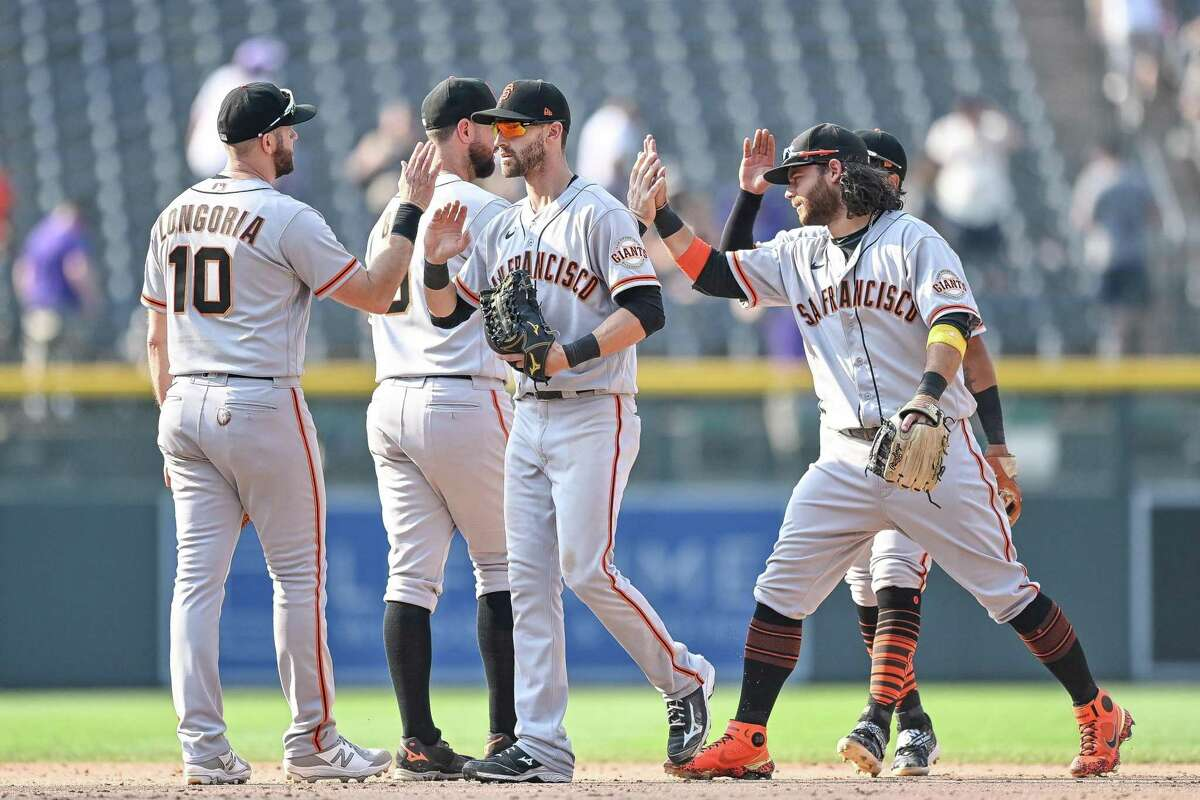 DENVER, CO - SEPTEMBER 8: San Francisco Giants players, including Evan Longoria #10, Steven Duggar #6, Brandon Belt #9, Brandon Crawford #35, and LaMonte Wade Jr. #31 celebrate after a 7-4 win against the Colorado Rockies at Coors Field on September 8, 2021 in Denver, Colorado. (Photo by Dustin Bradford/Getty Images)