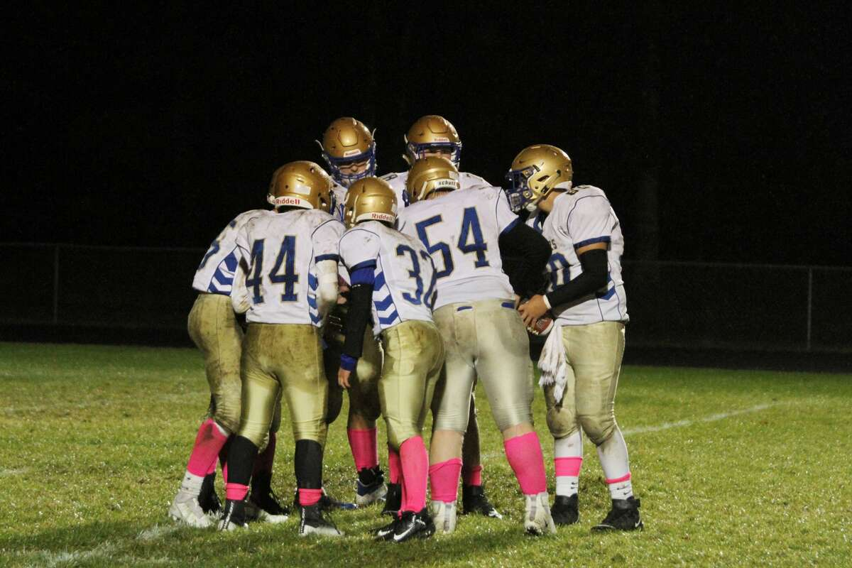 Onekama football huddles up in a loss to Brethren in 2020.