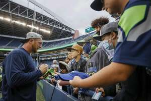 SEATTLE, WASHINGTON - AUGUST 21: Tight end Will Dissly #89 of the Seattle Seahawks signs autographs before an NFL preseason game against the Denver Broncos at Lumen Field on August 21, 2021 in Seattle, Washington. The Denver Broncos beat the Seattle Seahawks 30-3. (Photo by Steph Chambers/Getty Images)