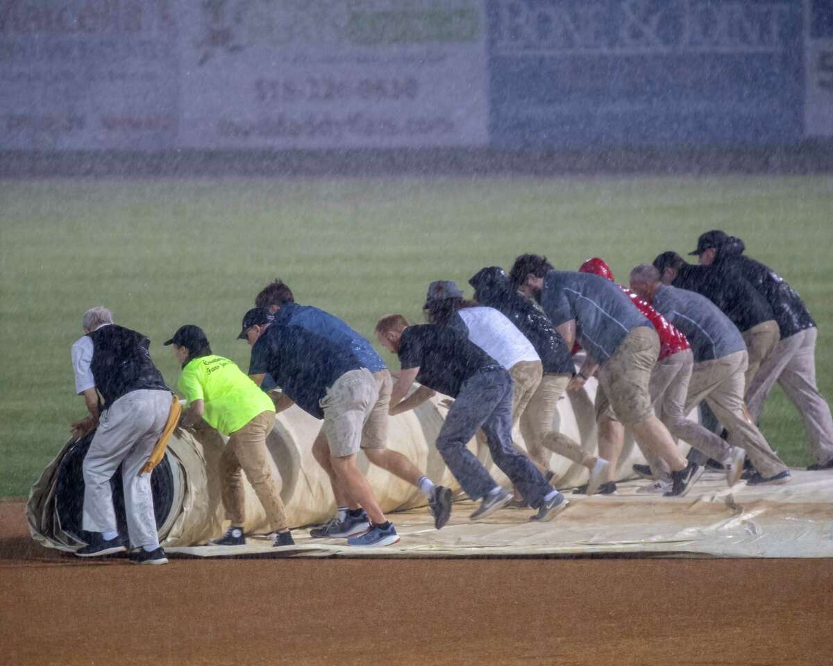 The Tri-City ValleyCats ground crew tries to cover the field during a game against the Sussex County Miners at Joseph L. Bruno Stadium on the Hudson Valley Community College campus in Troy, NY, on Wednesday, Sept. 8, 2021. The game was postponed until Thursday, Sept. 9, at 4 p.m. (Jim Franco/Special to the Times Union)