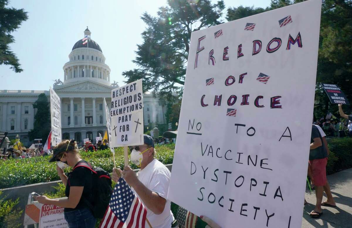 Protesters opposing vaccine mandates, which could be advanced again next year, march past the Capitol.