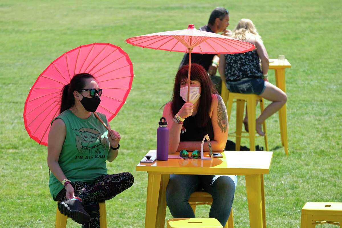 Two women wears masks and hold umbrellas while waiting for music to begin on the JaM Cellars JaMPad stage at the BottleRock Napa Valley music festival in Napa, Calif., Saturday, Sept. 4, 2021. (AP Photo/Eric Risberg)