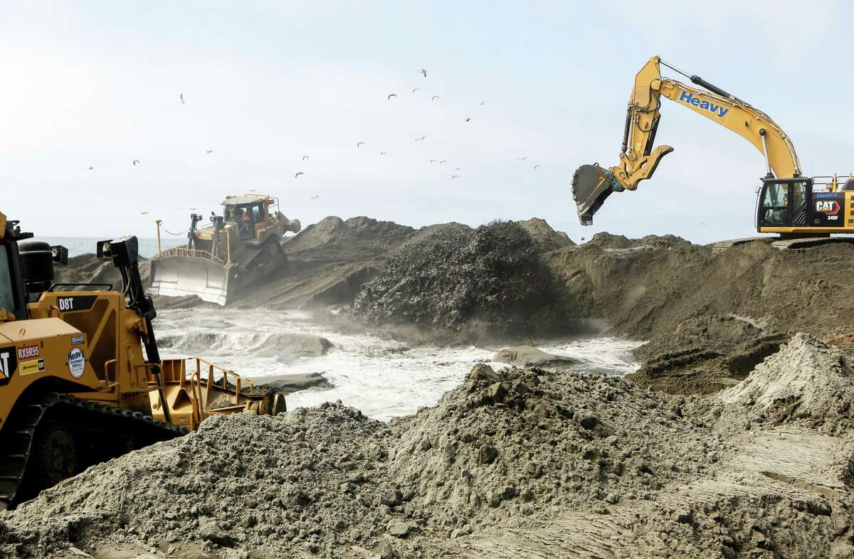 Bulldozers and excavators move sand in an effort to shield San Francisco's southern coast from rising sea levels.