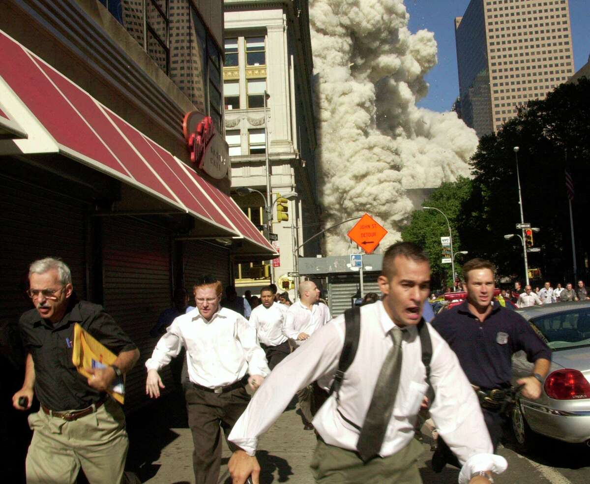 People run from the collapse of one of the twin towers at the World Trade Center in New York on Sept. 11, 2001.