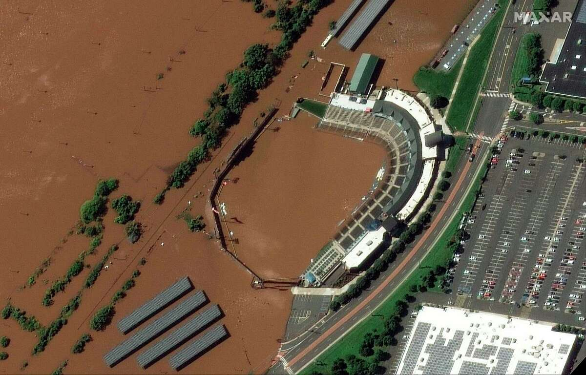 In a satellite image provided by Maxar Technologies, the stadium for the Somerset Patriots Double-A baseball team is partially flooded by overflow from the Raritan River on Thursday, Sept. 2, 2021, in Bridgewater Township, N.J., the day after torrential rain from the remnants of Hurricane Ida drenched the area. A railroad line to the left of the stadium is submerged. (Maxar Technologies via AP)
