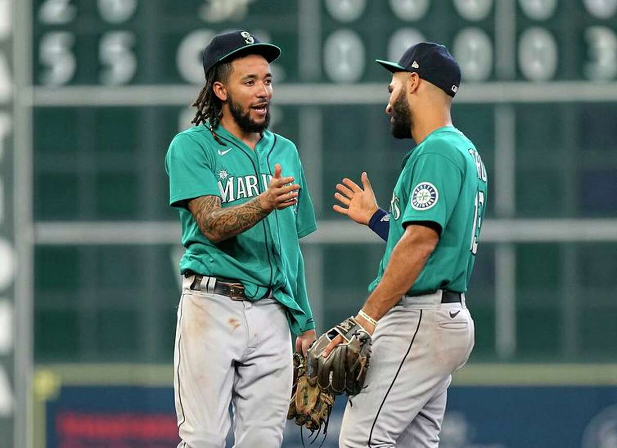 Mariners infielders J.P. Crawford and Abraham Toro celebrate after beating the Astros in Houston.