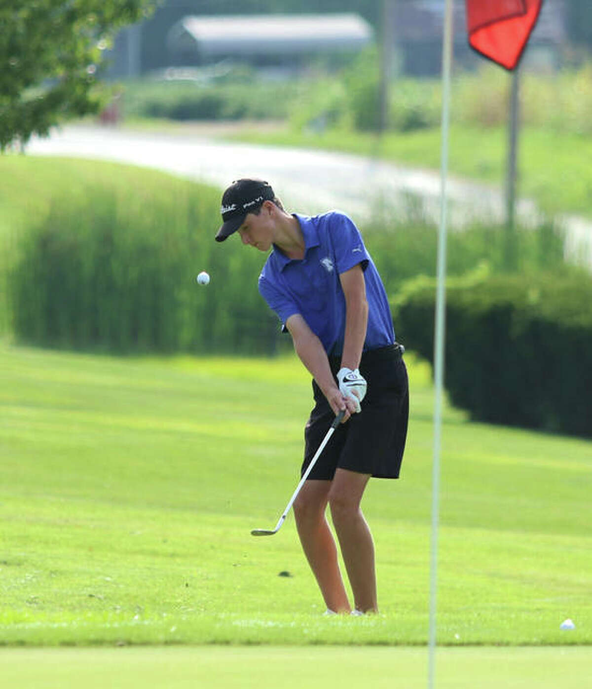Marquette Catholic's Aidan O'Keefe chips onto the green on hole No. 2 at Belk Park in the Hickory Stick Tourney on Aug. 16 in Wood River. On Wednesday, O'Keefe's even-par 36 led the Explorers to a one-shot dual victory over Alton High.