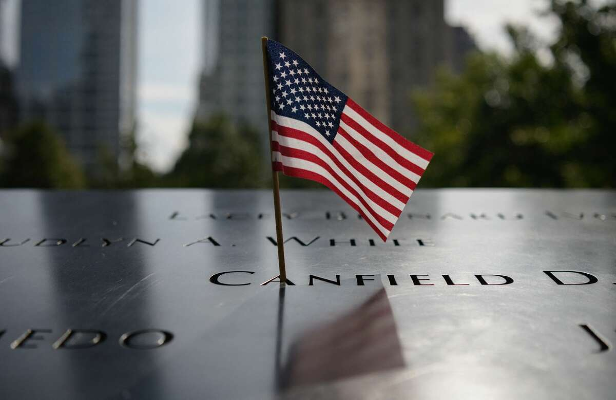 A US Flag adorns a name at the National September 11 Memorial site of the north tower at World Trade Center in New York, on September 8, 2021. (Photo by ANGELA WEISS/AFP via Getty Images)