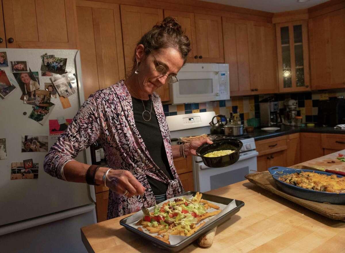 Caroline Barrett prepares Greek nacho french fries in her home in Delmar, N.Y.