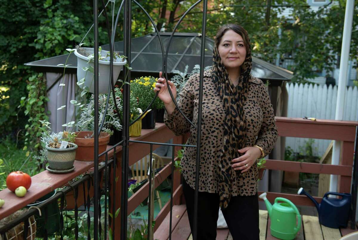 Shirin Karimi, a former refugee who came to the Capital Region from Afghanistan to build a new life for herself, stands on the deck in the back of her home on Wednesday, Sept. 8, 2021 in Albany, N.Y.