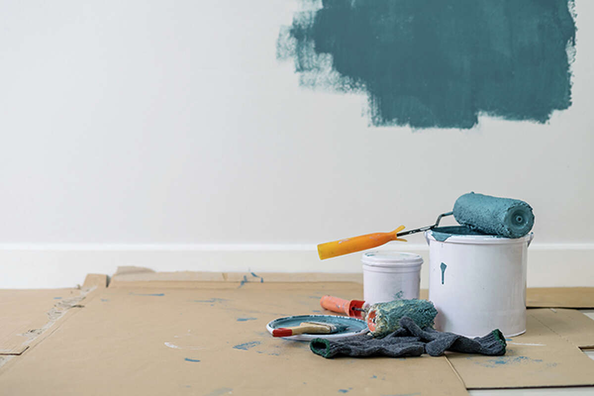 Pictured is a partially painted wall with a can of paint and tools.