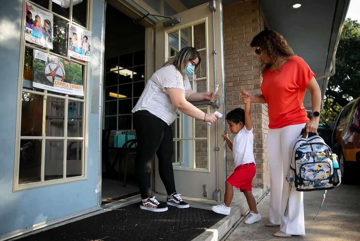 Child care supervisor Amy Davis takes the temperature of 3-year-old Nicholas as he is dropped off by his mother, Melissa Hurbs, at the Museum District Child Care Center in Houston on Sept. 1, 2021.