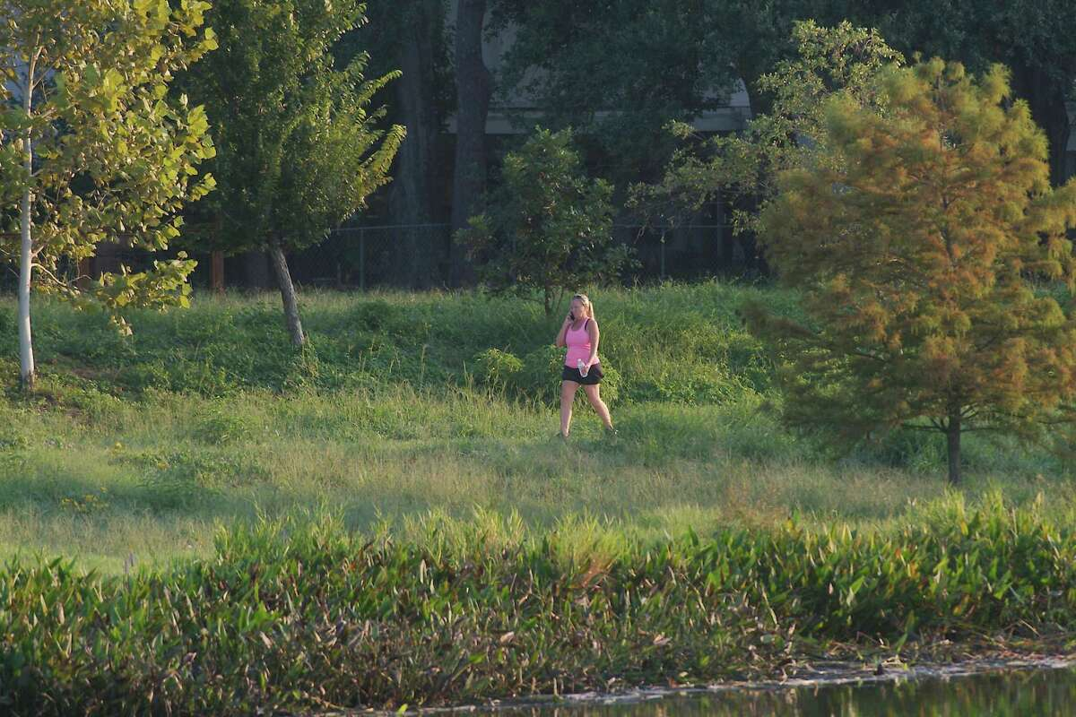 An Exploration Green visitor takes a morning stroll along a path that meanders around one of the detention lakes at the Clear Lake facility. Completion of final parts of a massive stormwater project is expected by the end of next year.