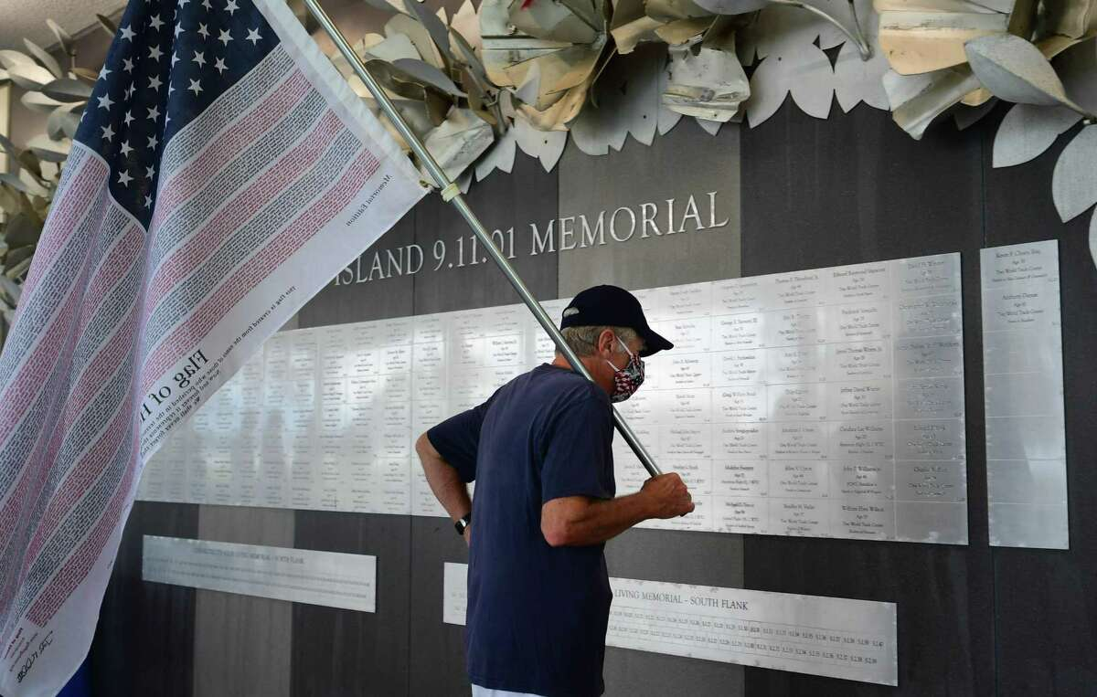 Bridgeport resident Fred Haschak looks at the names on the indoor memorial as Connecticut holds the 19th annual 9/11 memorial ceremony Thursday, September 10th, 2020, at Sherwood Island State Park in Westport, Conn. The ceremony is held yearly to honor and celebrate the lives lost in the Sept. 11, 2001 terror attacks. Family members of those killed in the attacks participated in the ceremony, and the names of the 162 victims with Connecticut ties were read aloud.