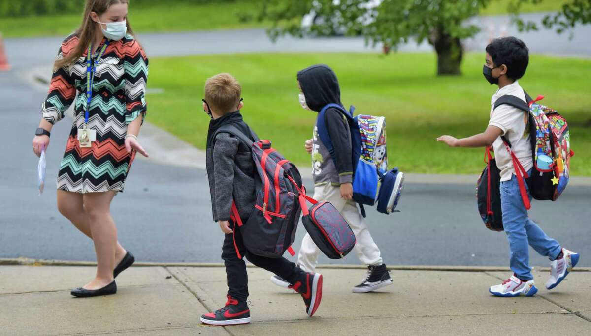 A staff member at Menands School walks children into the building on the first day of school on Thursday, Sept. 9, 2021, in Menands, N.Y.
