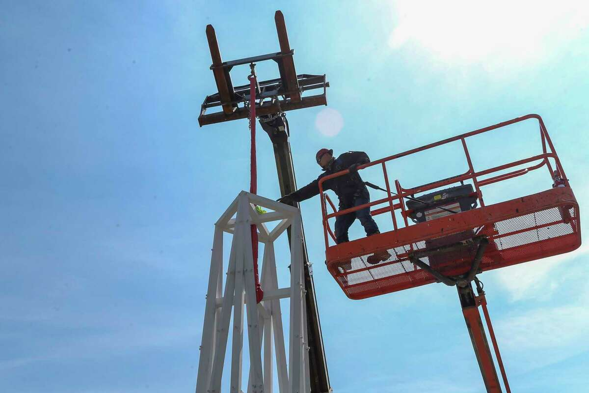 Crane operator Gilbert Carranza of Sunstate Equipment reaches out to the white tower component of the Peace monument at Clear Lake Park on September 8, 2021 in Houston, TX.