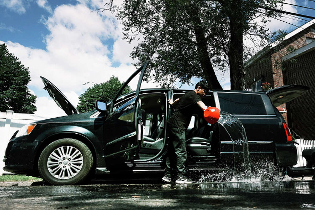 A teen cleans water out from a car in a flooded neighborhood.