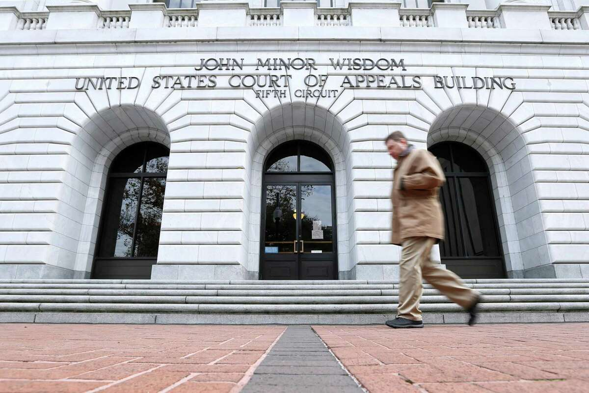 A man walks in front of the 5th U.S. Circuit Court of Appeals, Wednesday, Jan. 7, 2015, in New Orleans. The federal appeals court in New Orleans is considering whether a Texas law puts up an unconstitutional obstacle to women seeking abortions. (AP Photo/Jonathan Bachman)