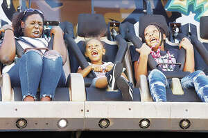 April Warren, left, and her two nieces — Kaliyah Warren, 7, center, and Kimora Curtis, 10, right — all of Alton, screamed through their entire ride on the Avalanche Wednesday night at the Alton Expo in Riverfront Park. The Alton Expo offers entertainment, rides and food through Sunday.