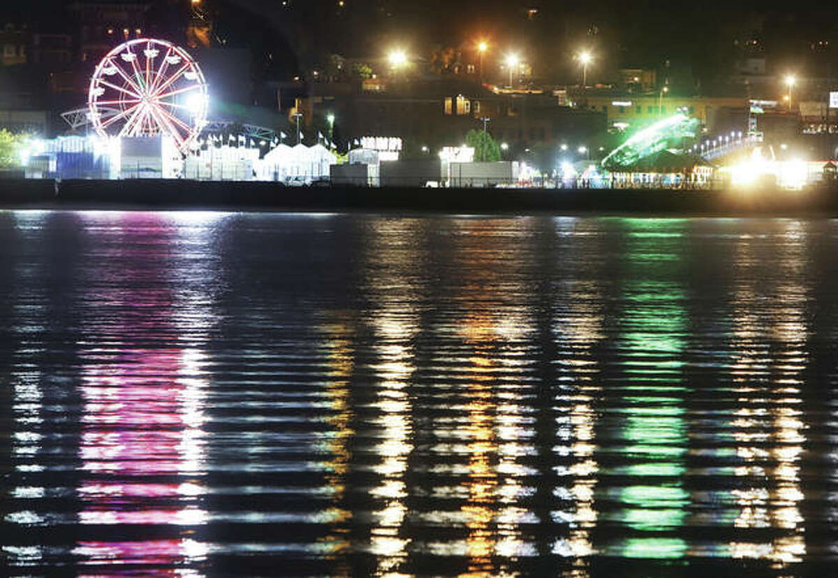 The carnival lights in Alton's Riverfront Park from the Alton Expo lit up the water Wednesday night, as seen from across the Mississippi River.