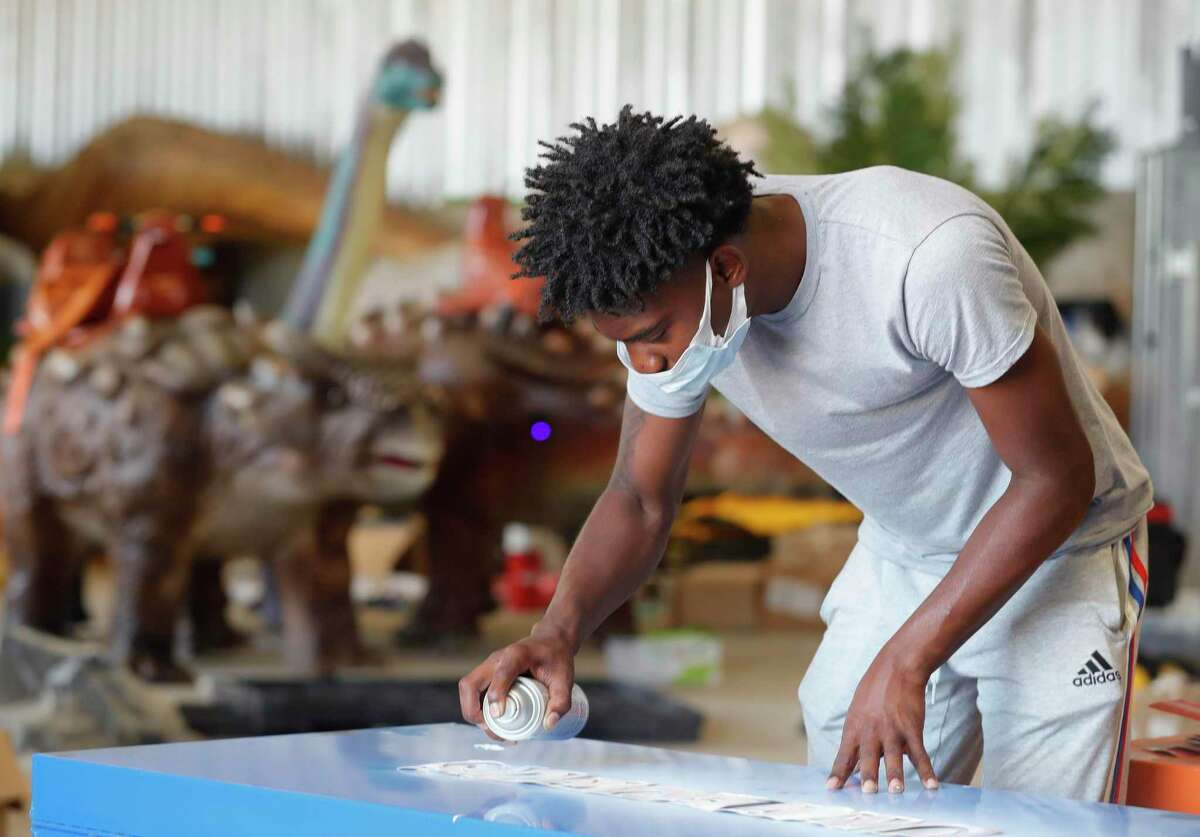 Jordan Ferell spray paints containers for gear at one of Jurassic Quest's warehouses, Tuesday, Sept. 7, 2021, in Tamina. Jurassic Quest is a traveling dinosaur attraction based near Conroe where guests walk through the Cretaceous, Jurassic and Triassic periods and experience for themselves what it was like to be among dinosaurs of all kinds.