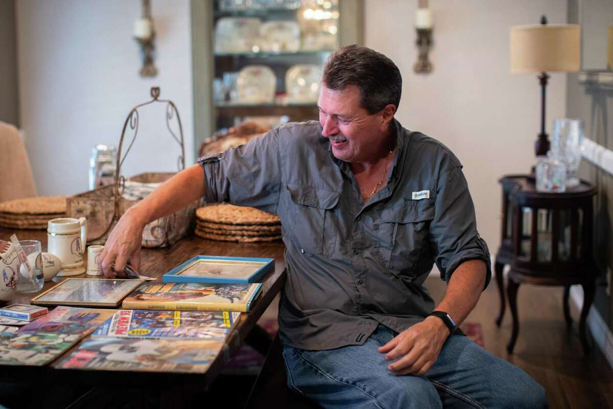 John Work, 64, former Houston Oilers and Texans season-ticket holder smiles as he goes over memorabilia he has saved from the time he used to attend the games.