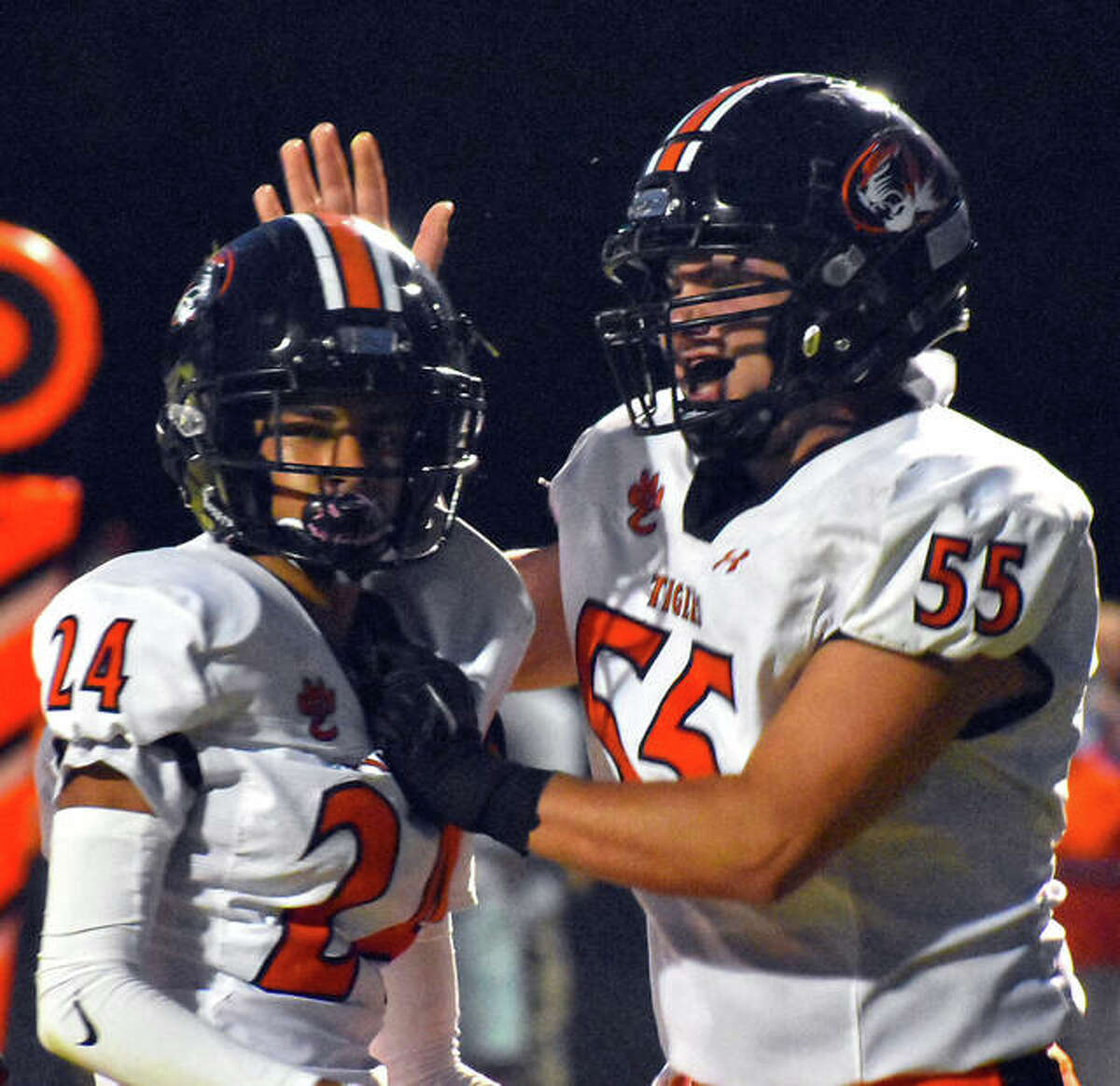 Edwardsville's David Deuanephenh, left, is congratulated by Austin Wolfe after scoring a touchdown in the second quarter against Highland on Friday.