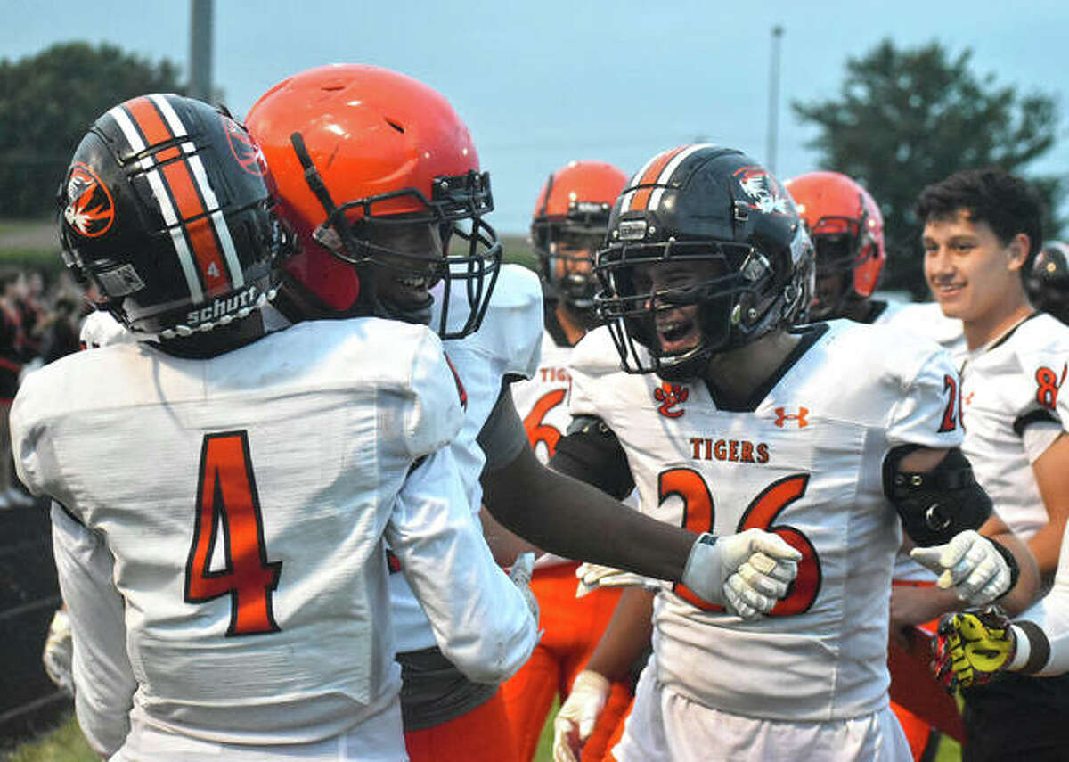 Edwardsville's Kellen Brnfre (No. 4) is welcomed back to the sideline by his teammates, including Luke Williams (No. 26) after returning a punt for a touchdown in the first quarter against Highland on Friday.