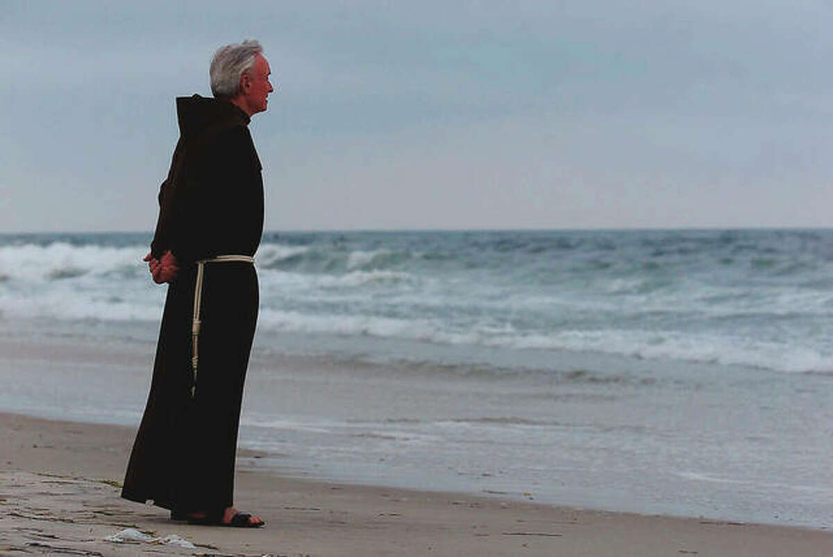 Father Mychal Judge, a chaplain with the New York City Fire Department, stands at the shore before a service where 230 candles were lit for the July 17, 1996, victims of TWA Flight 800. Judge left a uniquely complex legacy that continues to evolve 20 years after his death.