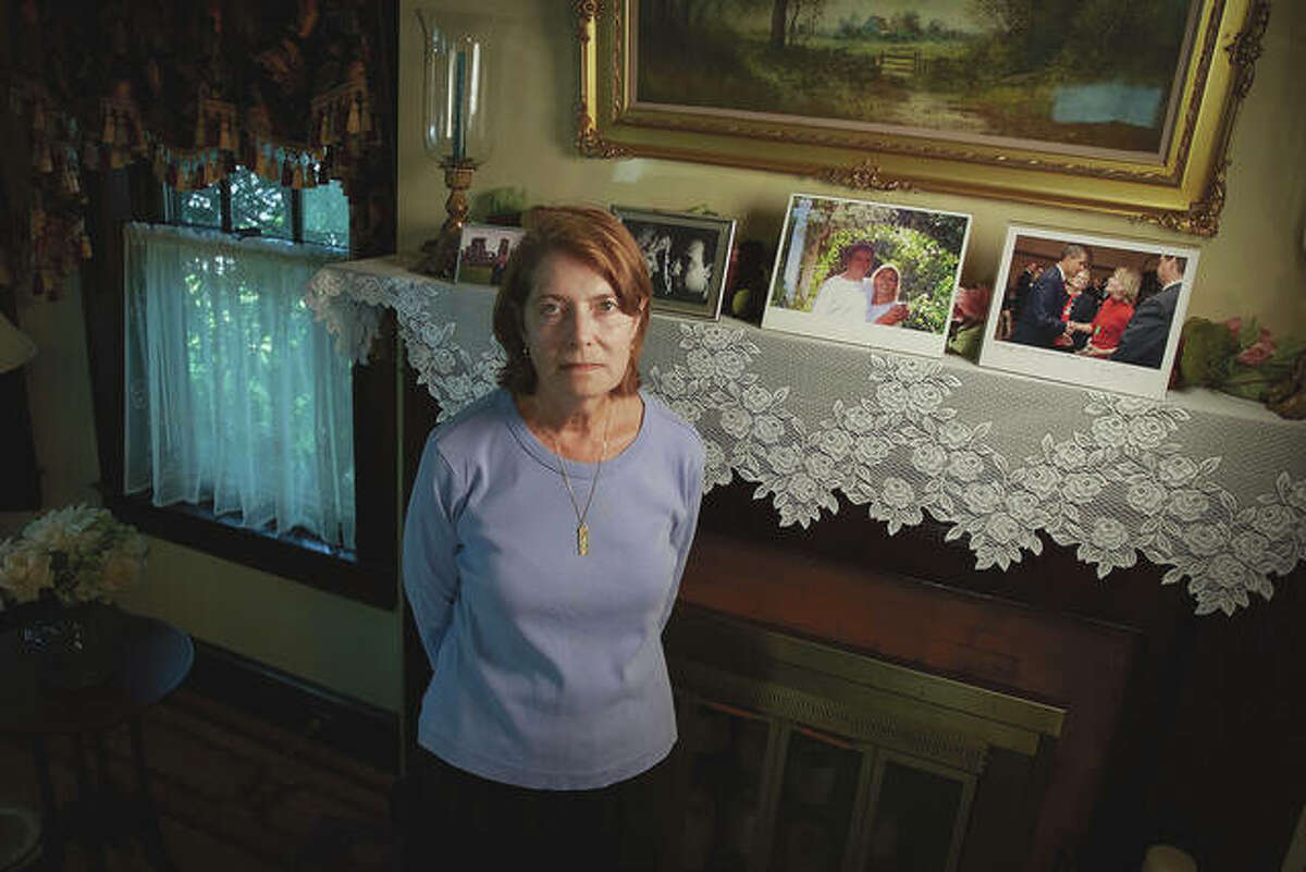 Margot Eckert stands by a display of pictures of her brother-in-law, Sean Rooney, and sister, Beverly Eckert, at her home.