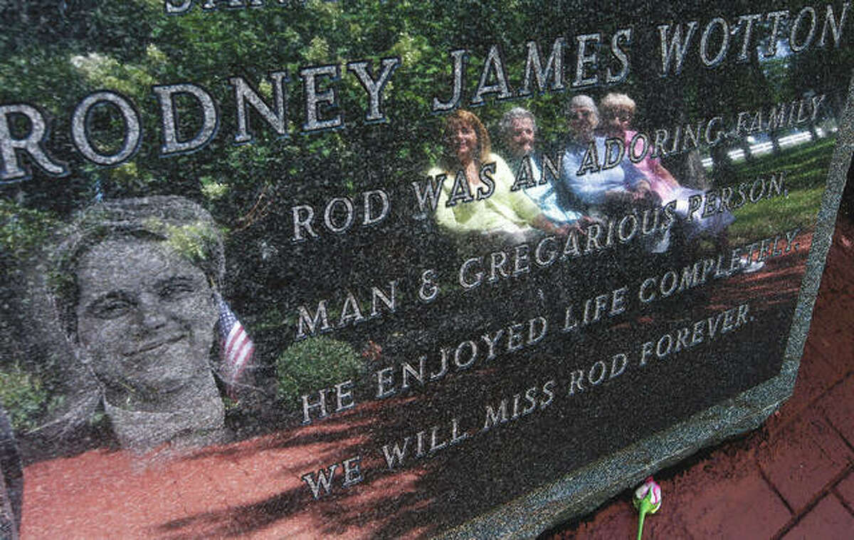 Pat Wotton (left) is reflected in a memorial to her husband, Rodney James Wotton, as she sits with Dorothy Greene (from left), Rodney's mother Jean Wotton and Eunice Saporito. The marker for Rodney Wotton is one of 37 in the Middletown World Trade Center Memorial Gardens.