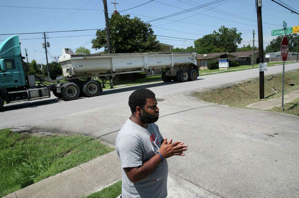 A semi-truck drives past Billy Lee, Jr., as he stands in front of the house he grew up in, Wednesday, Sept. 8, 2021, along Fidelity Street in Houston. Lee said he had concerns with air quality in the community. He said had spent most of his life in the community, and that he had seen many in the area develop health problems.