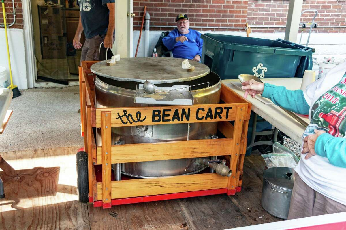 """Woody Raymond, the """"Bean Man,"""" pictured herebehind his giant bean pot,during the 2018 Founders Day, is preparing for his 13th year of making the famous bean soup for Founders Day this weekend. He is also looking for someone else to take over the job. (Photo provided)"""