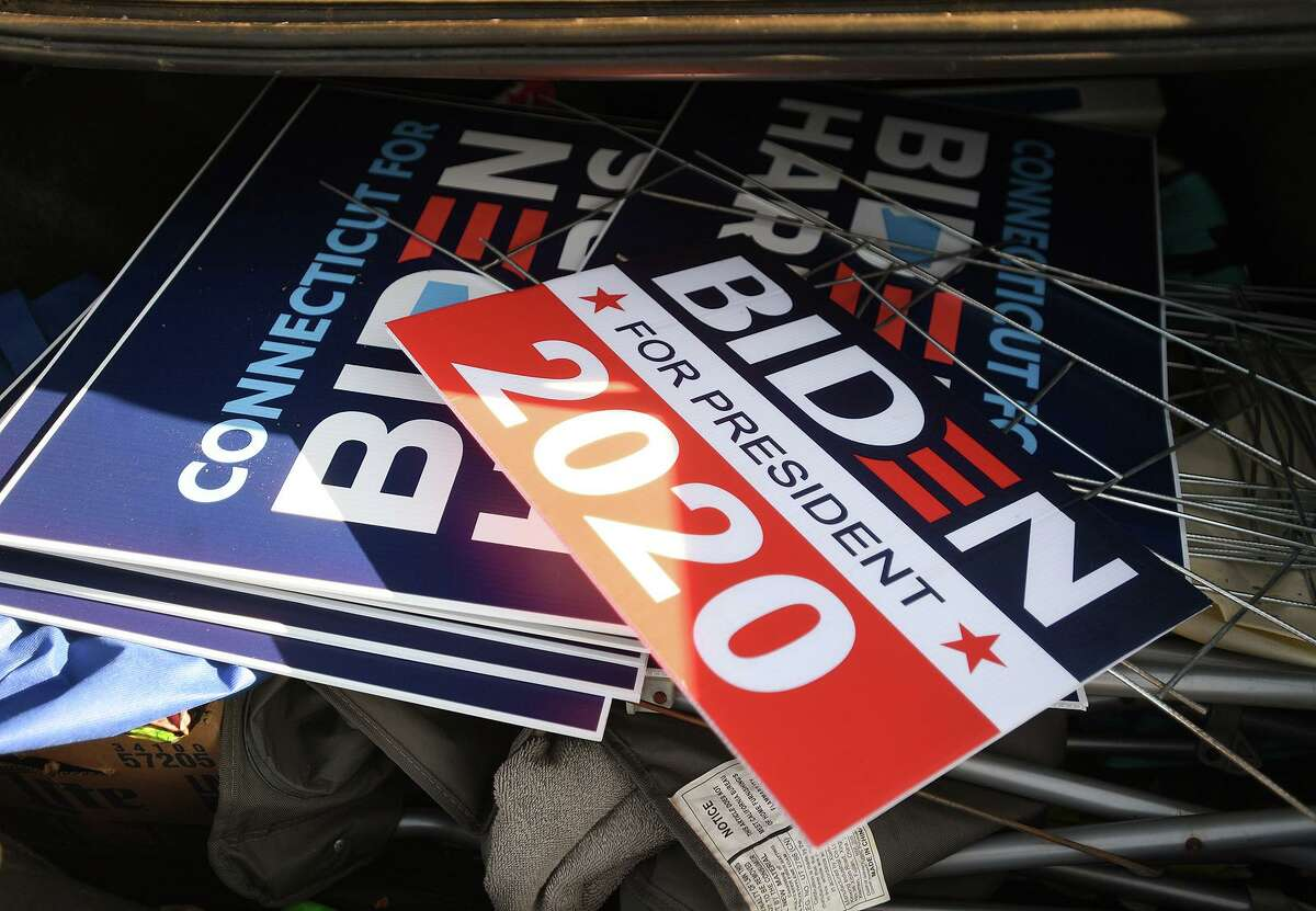 Campaign signs gathered from polling places fill a car trunk outside Democratic headquarters in Milford, Conn. on Wednesday, November 4, 2020.