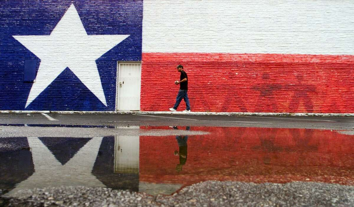 A man is reflected in a puddle as he walks past a mural of the Texas state flag, painted on the side of a building in Arlington, Texas.