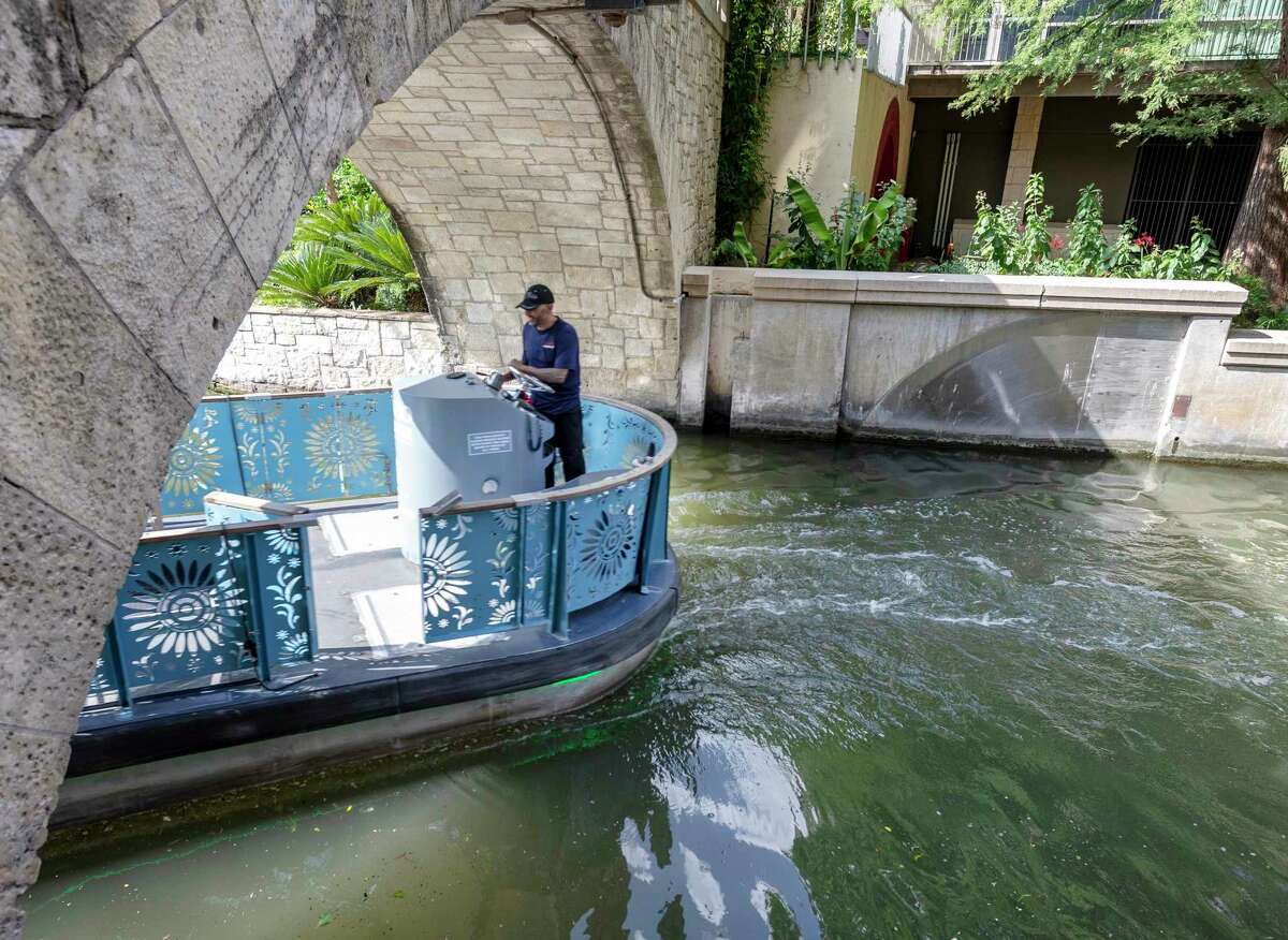 """A barge leaves the original San Antonio River channel Sept. 3, 2021, as it enters the """"cutoff channel"""" built in response to theSeptember 1921 flood that devastated downtown San Antonio. During flooding events an underwater gate rises up to keep water from enter the river's original channel."""