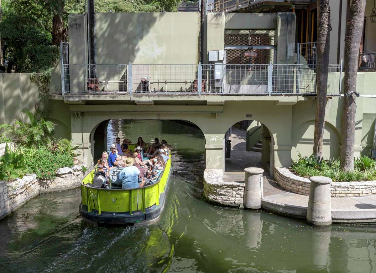 """A barge leaves the """"cutoff channel"""" Sept. 3, 2021, as it enters the original San Antonio River channel. The cutoff channel was built following the devastating September 1921 flood that devastated downtown San Antonio to protect businesses from future flooding. To keep the original channel from flooding a large gate lowers from the arch over the river separating the original river channel from the flood control system."""