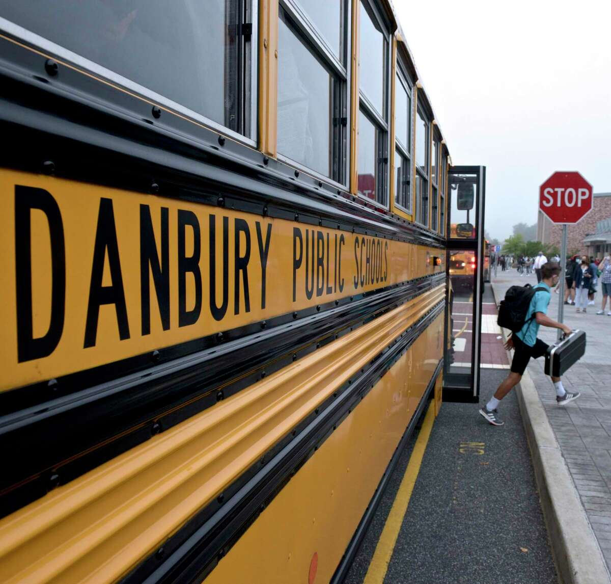 Students get of the busses at Danbury High School on the first day of the new school year. Monday, August 30, 2021, in Danbury, Conn.