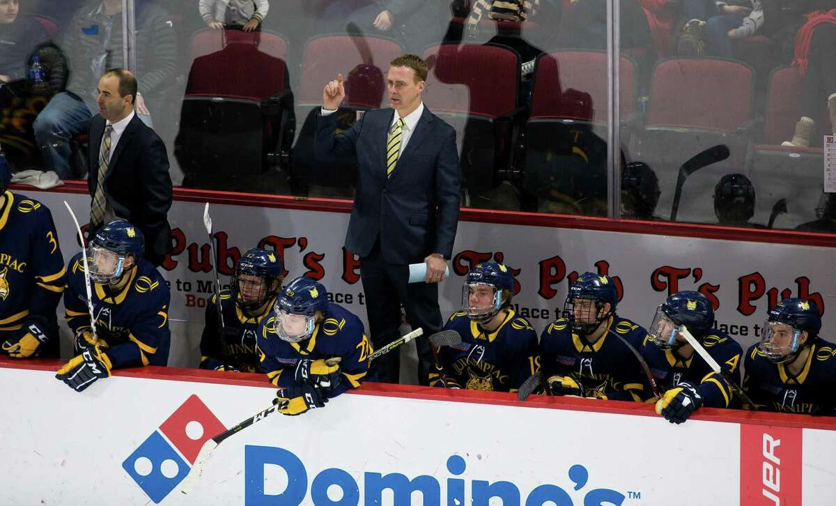 Qunnipiac men's hockey college Rand Pecknold stands behind the bench during a game against Boston University in 2019.