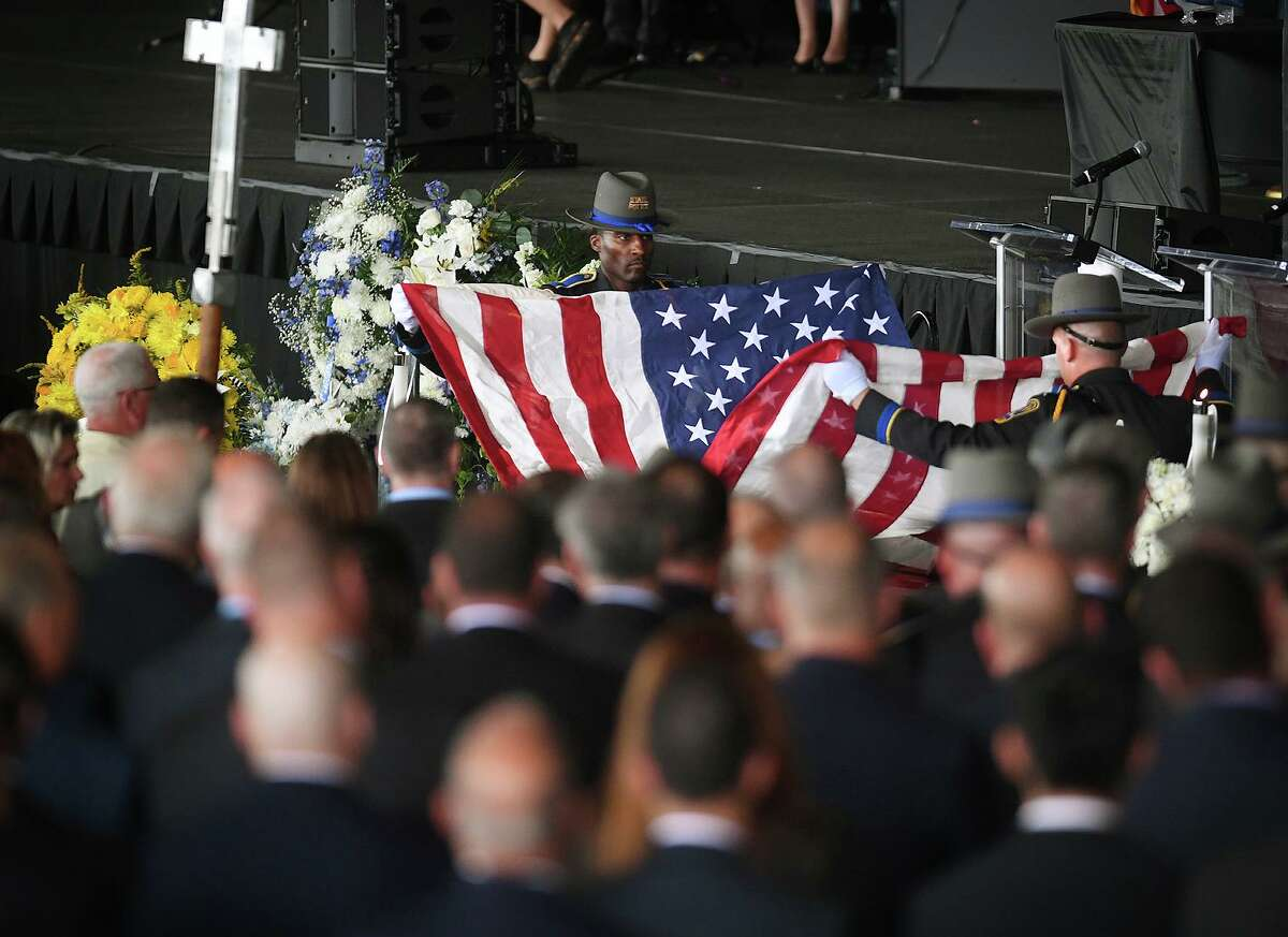State troopers fold the flag from the casket of fellow trooper Sgt. Brian Mohl during his funeral service at the Xfinity Theatre in Hartford on Thursday.