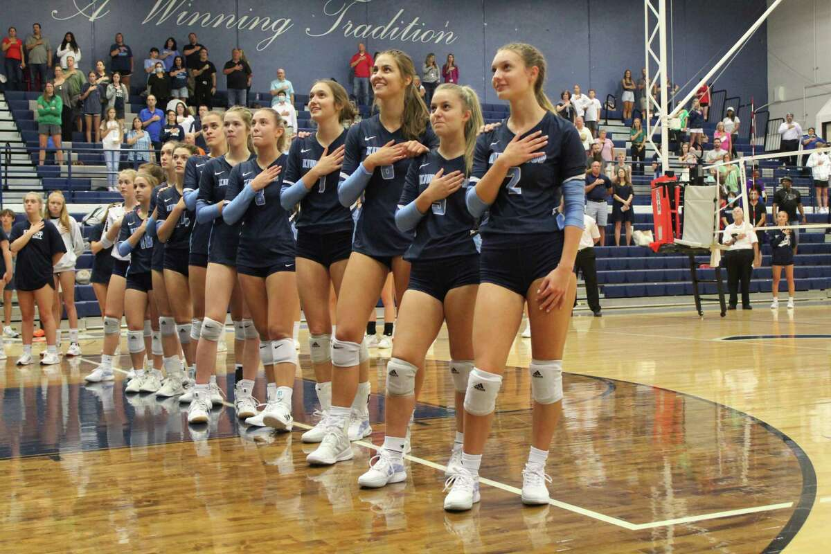 The 2021-2022 volleyball team during the national anthem at the Mustangs gym.